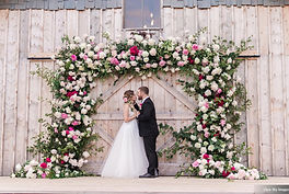 Bride and Groom under a Peony Arch at AK Diamond J Ranch Wedding Venues Barn. Arch create by Intrigue Designs