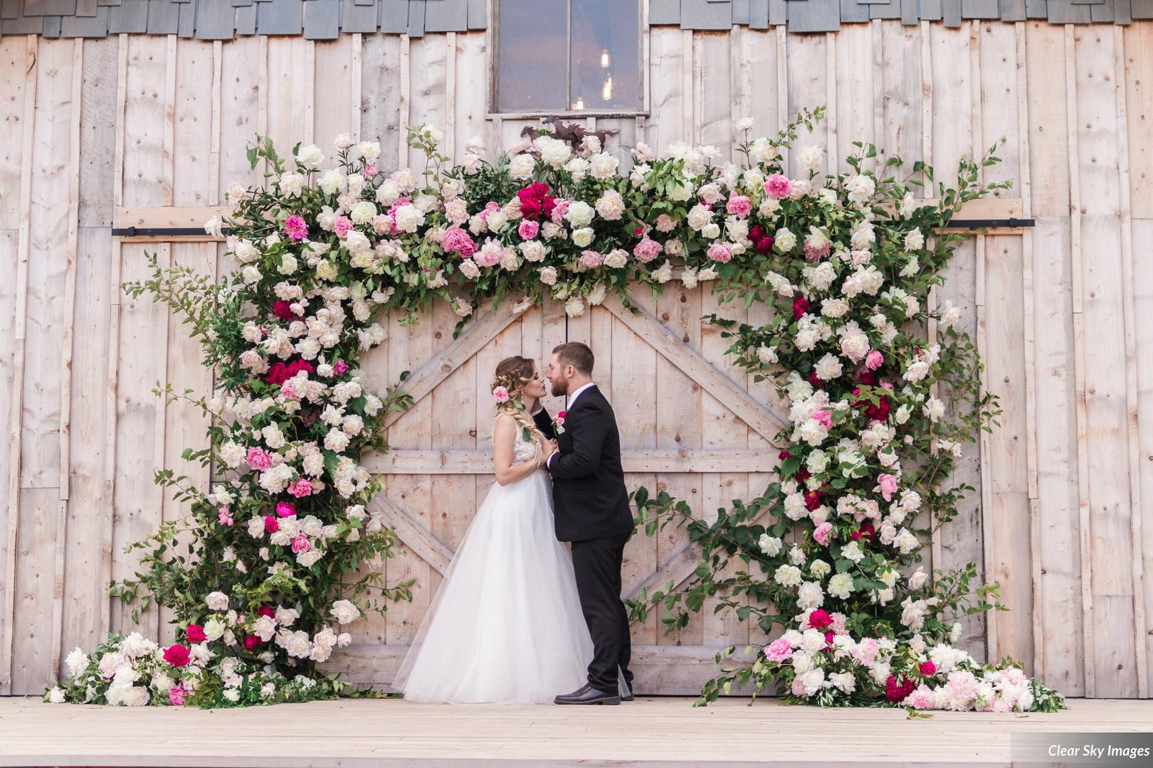 Bride and Groom on back deck of Heritage Barn, under peony arch by Intrigue Designs, Styled Shoots Across America