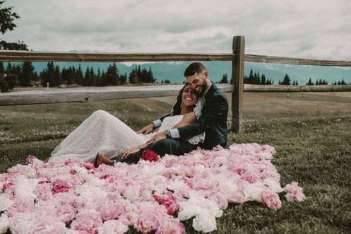 Bride and Groom on bed of peonies