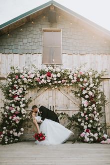 Bride and Groom on back deck of Heritage Barn with Intrigue Designs Peony Arch