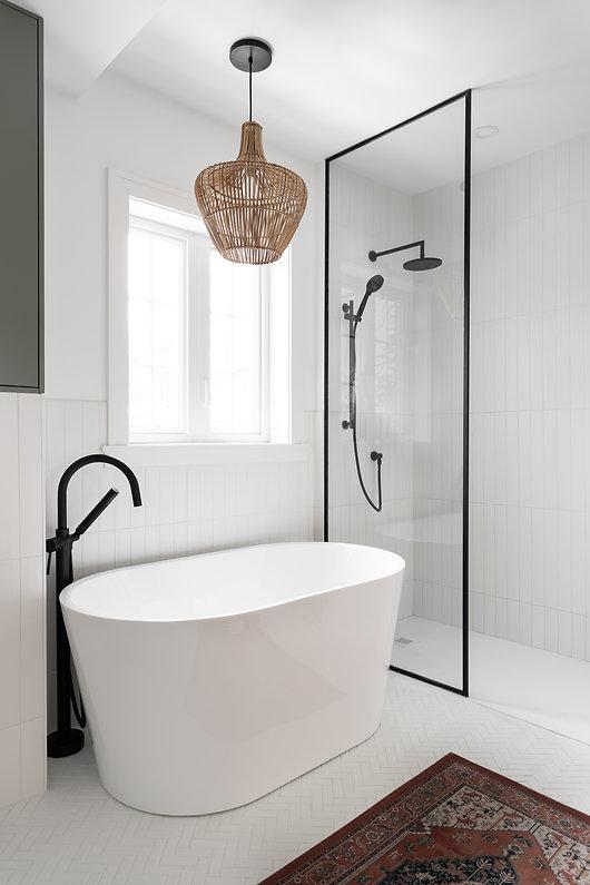les-stéphanies-chaleureux-salle-de-bain-baignoire-tuile-motif-mosaique-chevron-herrignbone-noir-panneau-verre-luminaire-osier-robinet-plomberie-noir-verre-tapis-céramique-vert