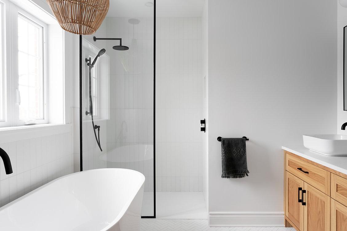 les-stéphanies-chaleureux-salle-de-bain-baignoire-tuile-motif-mosaique-chevron-herrignbone-noir-panneau-verre-luminaire-osier-robinet-plomberie-noir-céramique-vanité-chêne-blanc-bois