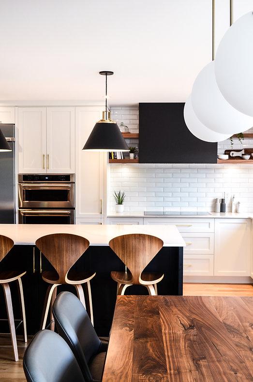 Cuisine blanche, cuisinemoderne, hotte métal, hotte noir, luminaire noir, tablette noyer, porte vitrée métal, tabouret noyer