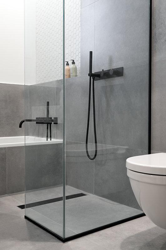 salle-de-bain-épurée-marbre-béton-blanc-noir-miroir-bain-podium-plomberie-noir