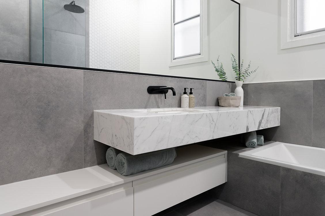salle-de-bain-épurée-marbre-béton-blanc-noir-miroir-bain-podium-lavabo-flottant-plomberie-noir