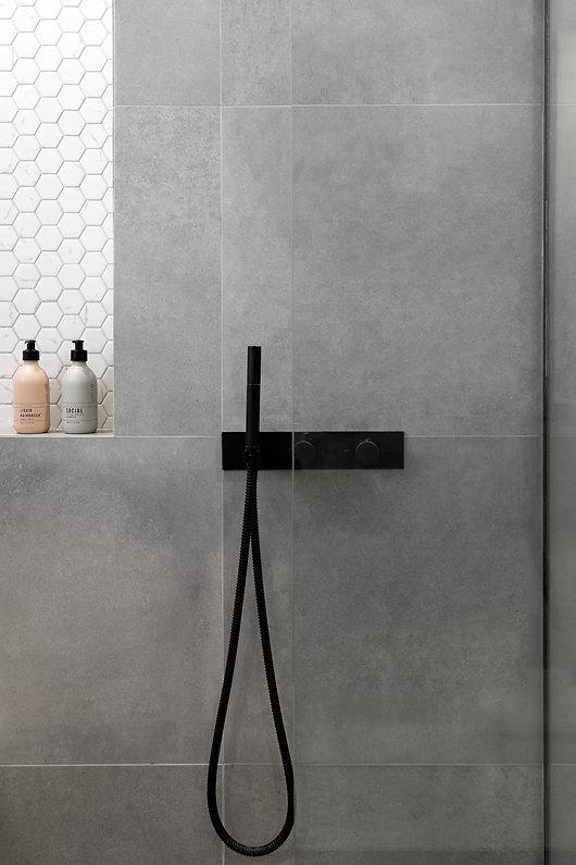 salle-de-bain-épurée-marbre-béton-blanc-noir-miroir-bain-podium-plomberie-noir-hexagone-tuile