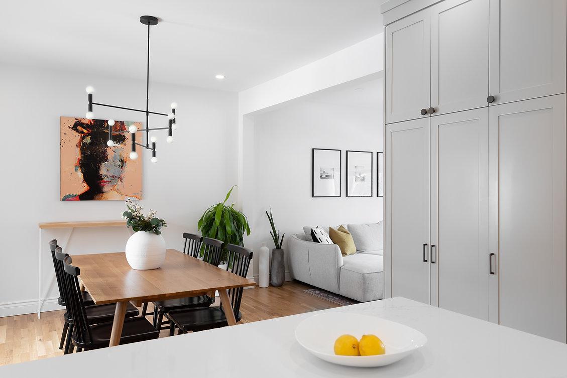 les-stéphanies-salon-blanc-contemporain-classique-moderne-salle-à-manger-table-chaises-noir-luminaire-armoires-cuisine-gris-grise-cadres-photos-oeuvre-d'art-quartz-comptoir