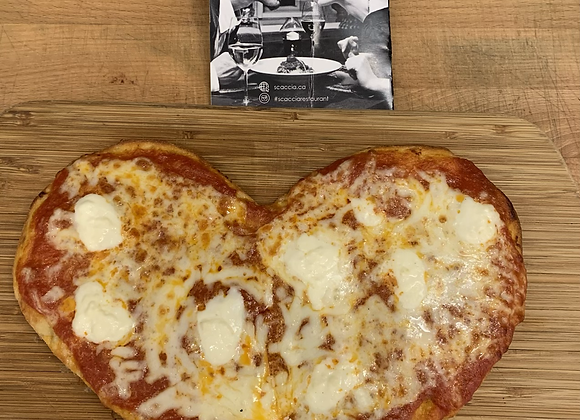 Heart shaped pizza on wood serving board