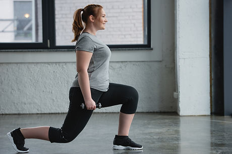Plus size woman performing lunges with dumbbell in gym.jpg