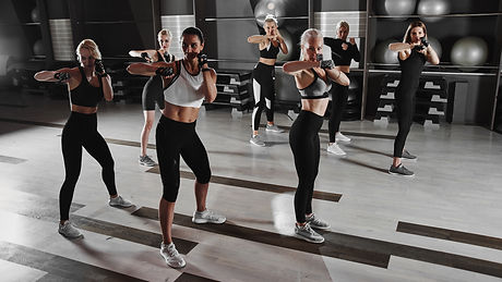 Women in black and white sportswear on a real group body Combat workout in the gym train t