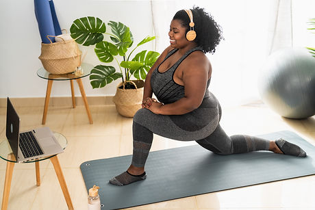 Young African woman doing pilates virtual fitness class with laptop at home - Sport wellne