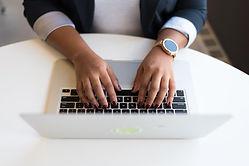 Both hands on keyboard of Mac laptop