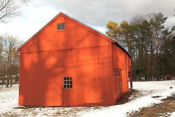 Red barn in snow, with shadows of bare tree branches