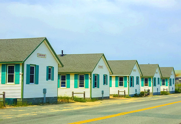 Row of white cottages with turquoise shutters