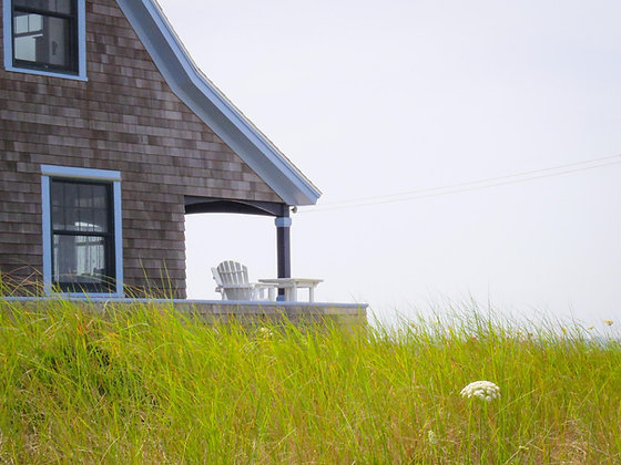 Weathered house on Cape Cod Bay, with a white Adirondack chair on the back porch