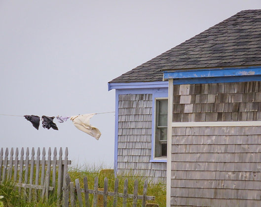 Weathered gray house on Cape Cod, with laundry on a clothesline