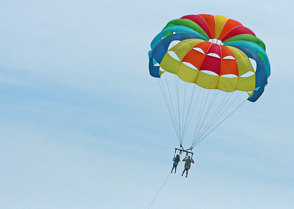 Two people suspended from a rainbow-colored parasail wing