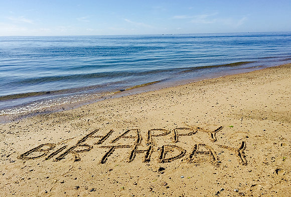 """Happy Birthday"" written in sand on a beach by the water"