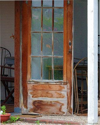 Weathered brown door with reflections in panes, Wellfleet, MA