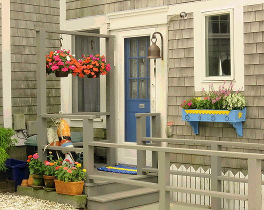 Several standing and hanging pots of flowers at the entrance to a gray shingled house with a blue door