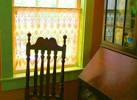 Antique chair and secretary beside curtained window