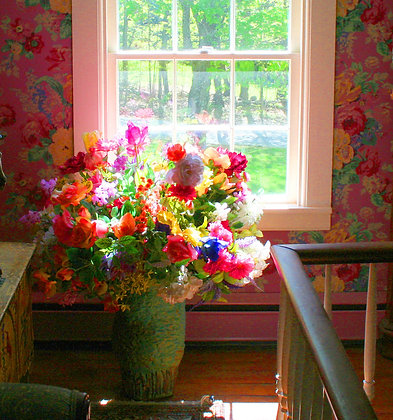 Silk flowers in vase by a window