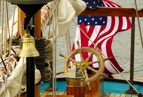 The helm of a sailing ship, with furled sail, brass bell, and an American flag