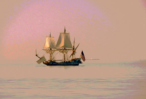 A sailing ship heads home in the pink sunset
