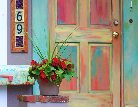 Multicolored painted door with pot of red geraniums