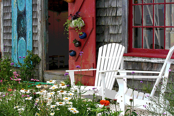 White Adirondack chairs in a garden outside a shop in Wellfleet