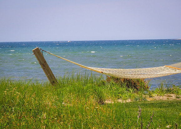 A rope hammock, with Cape Cod Bay in the background