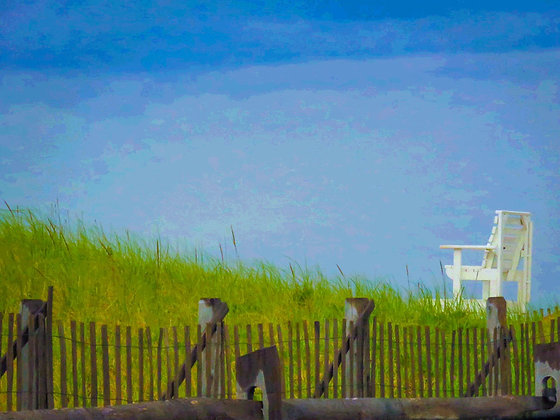 An empty white lifeguard chair in front of grass and a wood slat sand fence