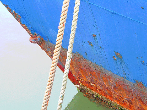 Detail of bow of a blue and red boat, with white rope in foreground