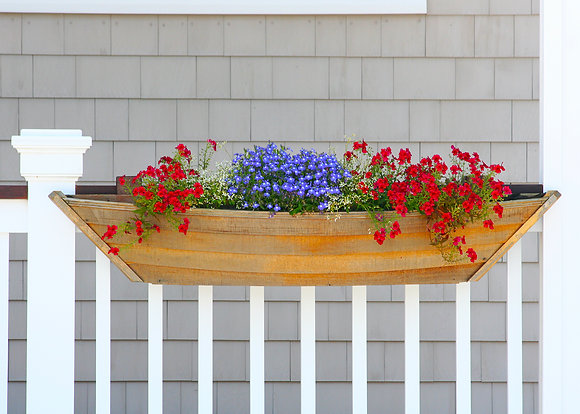 Blue and red flowers in a boat-shaped wooden planter mounted on a white railing