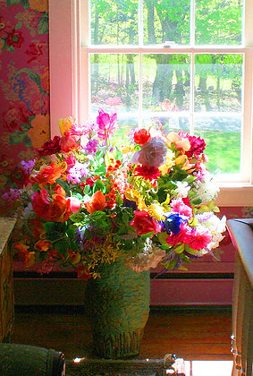 Vase of silk flowers beside window