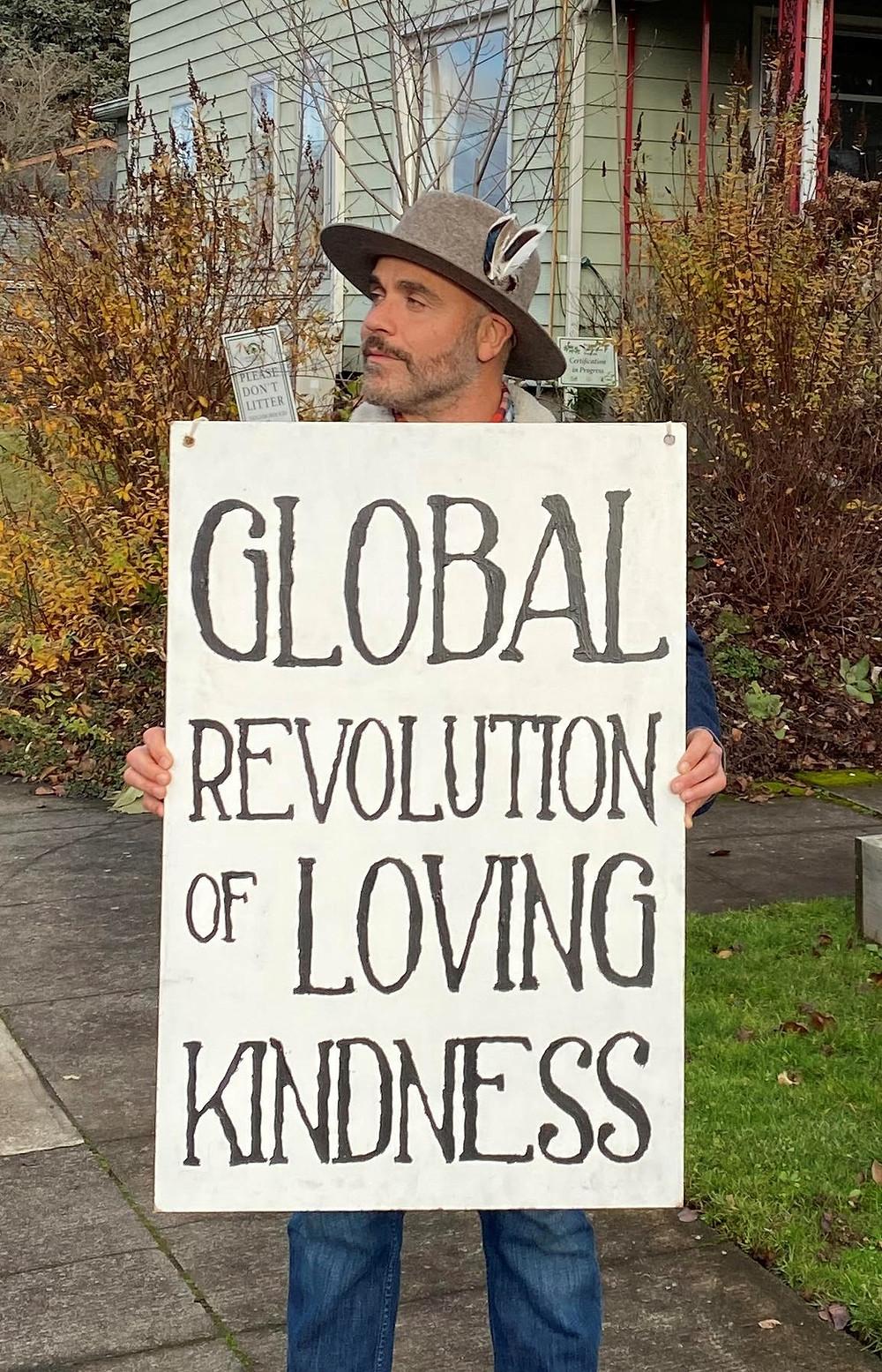Rozzell Medina holds a sign reading Global Revolution of Loving Kindness