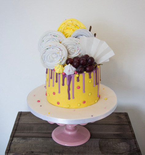 Bespoke drip cake with meringues.