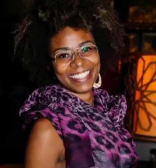 Mulher negra com cabelos crespos curtos. Usa óculos, blusa regata e lenço no pescço e sorri para nós.