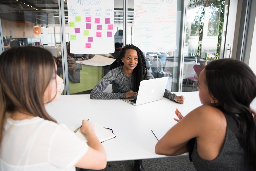 Mulheres conversam em uma sala de reuniões