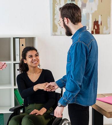 Mulher cadeirante em um escritório aperta a mão de um homem que a contratou para trabalhar
