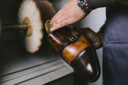 Shoemaker in workshop polishing new hand
