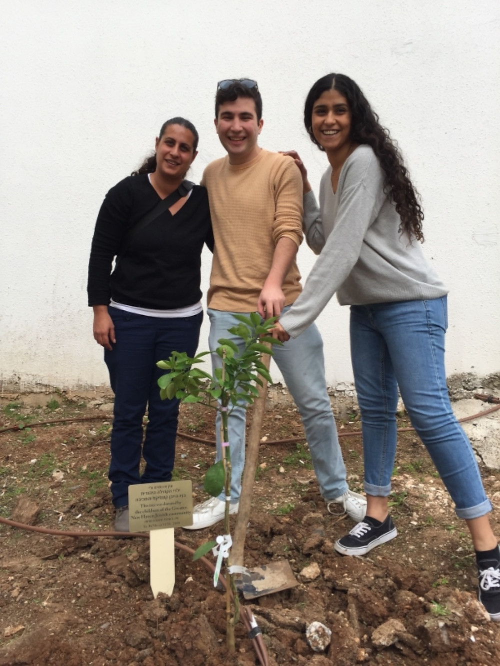 Shani, our first emissary, plants a tree with current emissaries Rotem and Talya, continuing the cycle of giving back to the Afula community