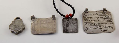 A selection of Persian, Egyptian and Moroccan amulets in silver and brass