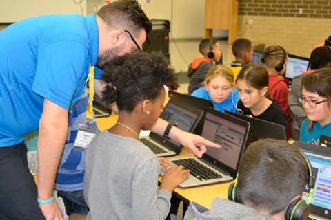 Hour-of-Code-mentor-assists-student_for-