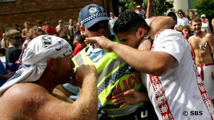 A police officer protests a victim in Cronulla's summer of simmering tension which boiled over into race riots in 2005