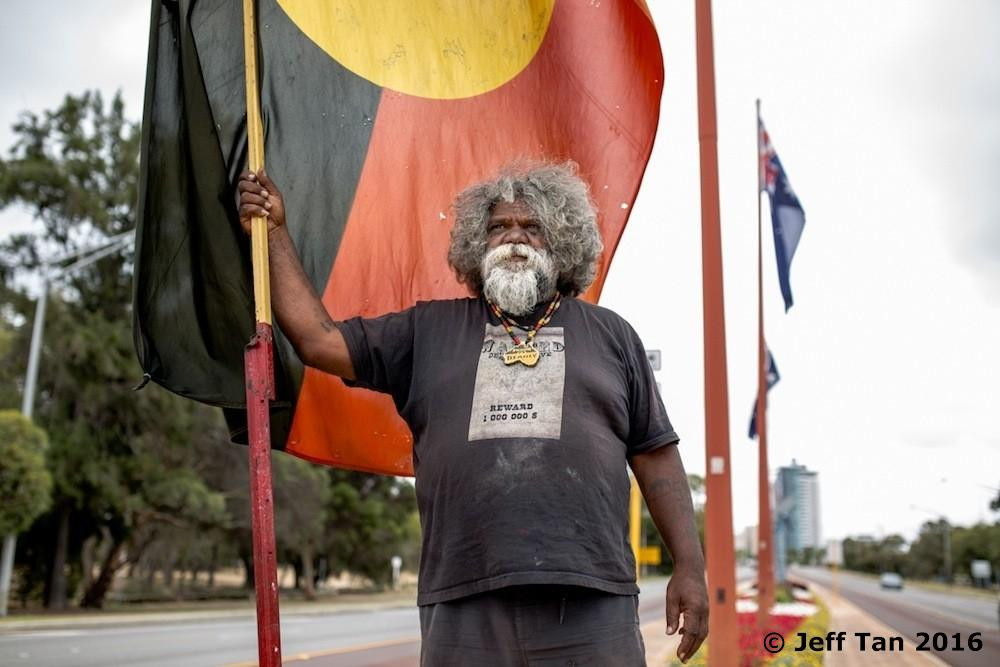 Herb Bropho proudly stands in the middle of the Causeway with the Aboriginal flag to defend Matagarup Refugee Camp Tent Embassy also known as Heirisson Island