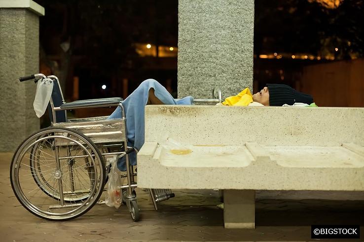 Homeless man in wheelchair sleeping roug