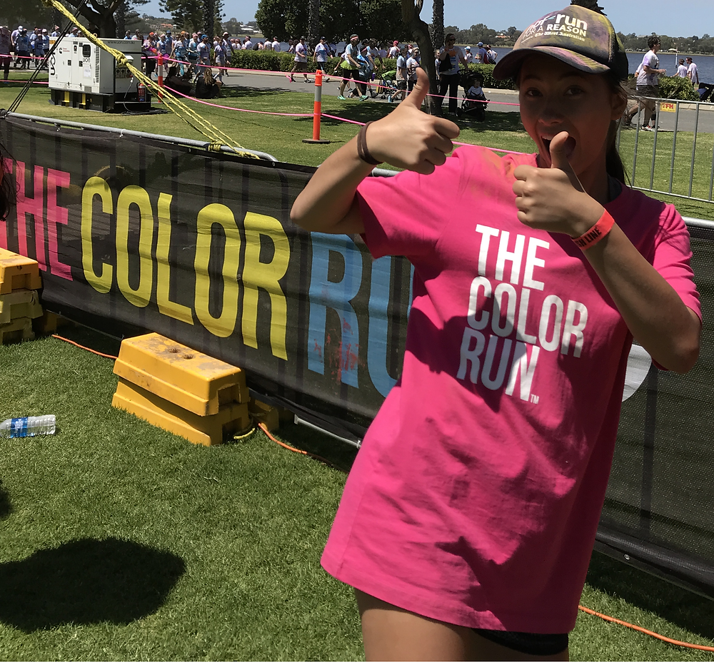 An awesome volunteer greets participants at the Finish Line Tunnel Perth Color Run five kilometer untimed event with colored powder - Delphine Jamet