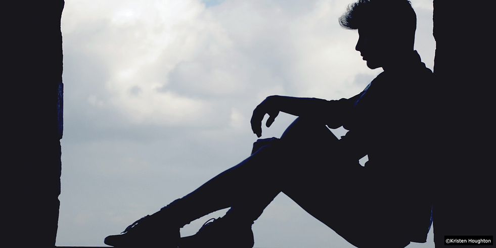 Teenaged boy sitting on the street homel
