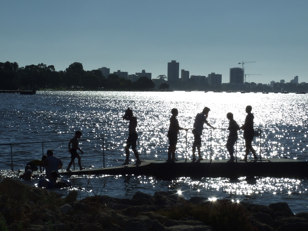 Children play on McCallum Park jetty by the river edge in South Perth on Australia Day waiting for The City of Perth Skyworks - Delphine Jamet